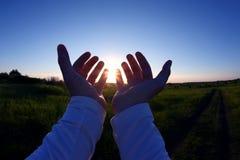 Para arriba levantadas manos en el fondo de la puesta del sol Foto de archivo libre de regalías