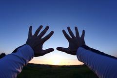 Para arriba levantadas manos en el fondo de la puesta del sol Fotos de archivo libres de regalías