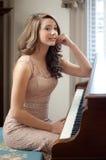 Para arriba vestida adolescente en el piano Fotografía de archivo