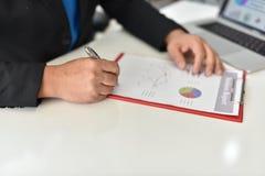 Para assinar, receba e aprove Mão do homem de negócio que aponta à informação do gráfico Imagens de Stock