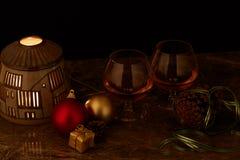 Para av exponeringsglas av starksprit på den dekorerade jultabellen med stearinljuslampan och svart bakgrund arkivbilder