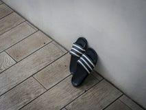 Para błękitni i biali plastikowi sandały opiera przeciw ścianie outdoors zdjęcie stock