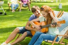 Para bawić się gitarę przy obozem zdjęcie royalty free