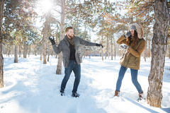 Para bawić się z śniegiem w zima parku Zdjęcia Stock