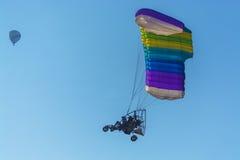 Para-Bewegungssegelflugzeug und Heißluft steigt das Beleidigen im Ballon auf Stockbilder