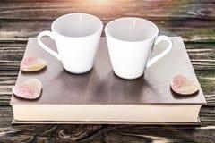Para biel kubki dla kawy na książce zdjęcia stock