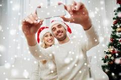 Para bierze selfie z smartphone przy bożymi narodzeniami zdjęcia royalty free
