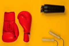 Para bokserskie rękawiczki obok bidonu i skok arkany na żółtym tle zdjęcia royalty free