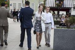 Para chodzi w dół ulicę Dziewczyna jest ubranym w kratkę szarości spódnicę i białą bluzkę Młody człowiek w białej klasycznej kosz Obrazy Stock