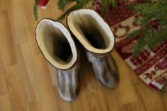 Para ciepłych butów zakończenie w wełna stojakach blisko choinki z teraźniejszość na drewnianej podłoga w domu obok candleligh Obrazy Stock