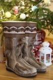 Para ciepłych butów zakończenie w wełna stojakach blisko choinki z teraźniejszość na drewnianej podłoga w domu obok candleligh Zdjęcie Stock