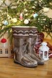 Para ciepli buty w wełna stojakach blisko choinki z teraźniejszość na drewnianej podłoga w domu obok blasku świecy i r Obraz Stock
