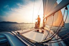 Para cieszy się zmierzch od żagiel łodzi obraz stock