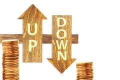 Para cima e para baixo o texto na seta de madeira no fundo branco com moeda Foto de Stock Royalty Free