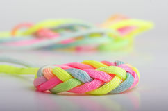 Para cord braided into a decorative knot. In bright neon colors stock photos