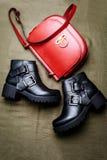 Para czarni rzemienni buty z niskimi pi?tami i czerwon? torb? na zielonym tkaniny tle zdjęcia royalty free