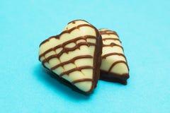 Para czekoladowi cukierki w formie serc, na błękitnym tle zdjęcia royalty free