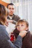 Para daje kaszlowemu syropowi cierpiąca chłopiec Obrazy Stock