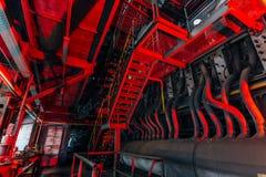 Para dentro da fábrica abandonada velha Conexão industrial arruinada oxidada do encanamento Fundo industrial iluminado vermelho d foto de stock