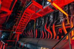 Para dentro da fábrica abandonada velha Conexão industrial arruinada oxidada do encanamento Fundo industrial iluminado vermelho d imagem de stock