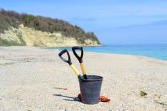 Para despejar las herramientas de la ?arth-limpieza en la playa vacía Fotos de archivo