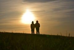 Para dos personas delante de la puesta del sol foto de archivo libre de regalías