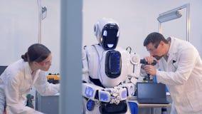 Para dos personas examine la condición del ` s del robot almacen de video