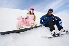 Para dos personas siéntese en nieve y la preparación montar Fotografía de archivo