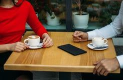 Para, dwa, facet i dziewczyna, siedzimy w cukiernianym, pijący kawę, dwa filiżanki cappuccino na stole, rachunek dla napoju zdjęcia stock