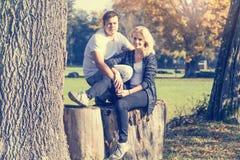 Para dwa młodzi ludzie w miłości siedzi na drewnie Zdjęcia Stock