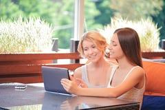 Para dziewczyny w kawiarni z pastylką obraz royalty free
