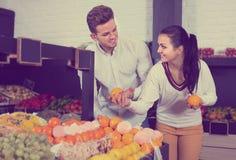 Para egzamininuje różnorodne owoc w sklepie spożywczym fotografia stock