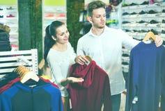 Para egzamininuje różnorodnych sporty odziewa w sporta sklepie Obrazy Royalty Free