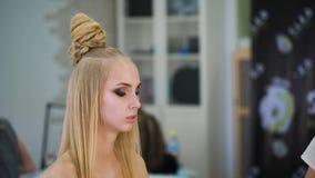 Para el blonde sensual en un salón de belleza que hace maquillaje Acentúa los ojos con las sombras metrajes