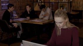 Para el ordenador portátil en café una mujer joven aprende y trabaja entre gente almacen de metraje de vídeo