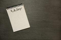Para fazer hoje aliste no bloco de notas espiral gridded urgente - na ardósia escura foto de stock