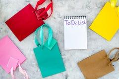 Para fazer a lista para comprar no caderno entre os sacos de compras de papel na opinião superior do fundo cinzento Fotos de Stock Royalty Free
