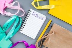 Para fazer a lista para comprar no caderno entre os sacos de compras de papel na opinião superior do fundo cinzento Fotos de Stock