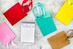Para fazer a lista para comprar no caderno entre os sacos de compras de papel na opinião superior do fundo cinzento Fotografia de Stock Royalty Free