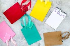 Para fazer a lista para comprar no caderno entre os sacos de compras de papel na opinião superior do fundo cinzento Imagem de Stock Royalty Free