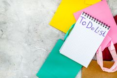 Para fazer a lista para comprar no caderno perto dos sacos de compras de papel no copyspace cinzento do modelo da opinião superio Foto de Stock