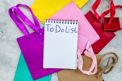 Para fazer a lista para comprar no caderno perto dos sacos de compras de papel no modelo cinzento da opinião superior do fundo Foto de Stock Royalty Free