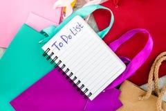 Para fazer a lista para comprar no caderno perto dos sacos de compras de papel no modelo cinzento da opinião superior do fundo Imagens de Stock Royalty Free