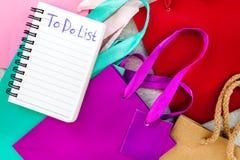 Para fazer a lista para comprar no caderno perto dos sacos de compras de papel no modelo cinzento da opinião superior do fundo Imagem de Stock