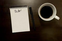 Para fazer a lista no bloco de notas espiral gridded com pena e xícara de café - na madeira escura foto de stock