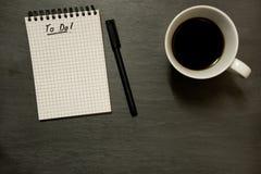 Para fazer a lista no bloco de notas espiral gridded com xícara de café, no tampo da mesa da ardósia - de cima de, mínimo foto de stock royalty free