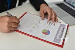 Para firmar, reciba y apruebe Mano del hombre de negocios que señala a la información del gráfico fotografía de archivo
