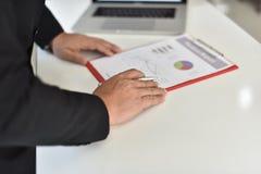 Para firmar, reciba y apruebe Mano del hombre de negocios que señala a la información del gráfico fotografía de archivo libre de regalías