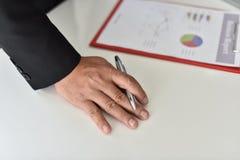 Para firmar, reciba y apruebe Mano del hombre de negocios que señala a la información del gráfico imagen de archivo
