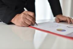 Para firmar, reciba y apruebe Mano del hombre de negocios que señala a la información del gráfico fotos de archivo libres de regalías